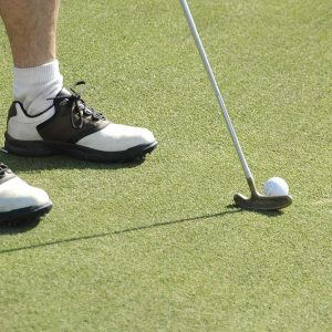 A golfer about to put on a fake grass putting green
