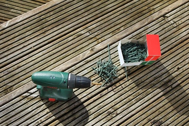 A drill and screws on some decking boards